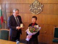 Плакет и цветя в знак на благодарност от кмета Спартански за Мария Мескин
